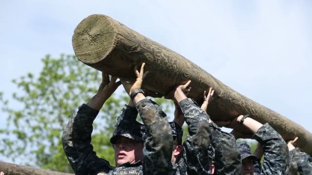 Mid shot members of the United States Naval Academy freshman class carry a heavy log as they participate in the annual Sea Trials Annapolis Maryland...