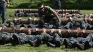 Mid shot members of the United States Naval Academy freshman class do situps as a team with heavy logs as they participate in the annual Sea Trials...