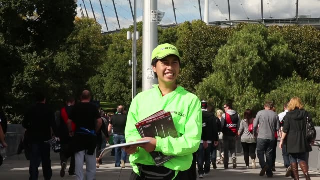 Mid shot of a footy Record salesman holds a copy of the Record aloft before the AFL Anzac Day match between the Essendon Bombers and the Collingwood...