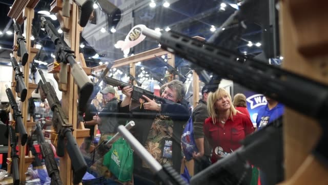 Mid shot of a middle aged woman practice aiming with a assault rifle during the 2013 NRA Annual Meeting and Exhibits at the George R Brown Convention...