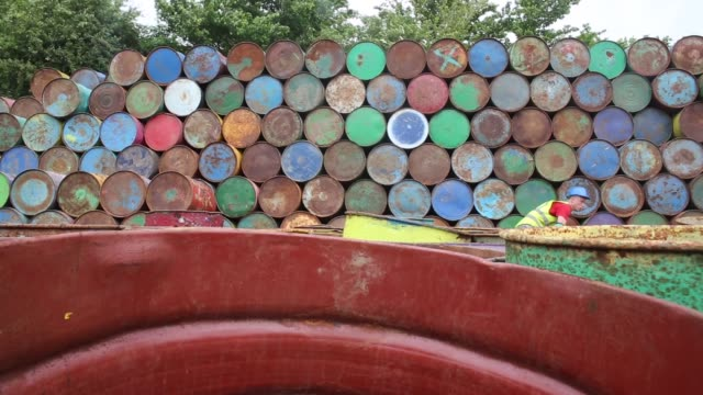 Mid shot of a worker unstacking metal barrels