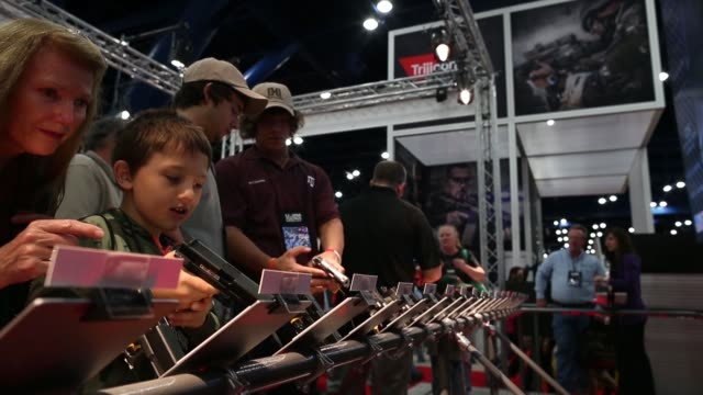 Mid shot of exhibition attendants trying out revolvers during the 2013 NRA Annual Meeting and Exhibits at the George R Brown Convention Center on May...