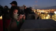 Mid Shot people photograph the view from the Top of the Rock observation deck in Midtown Manhattan the Empire State Building and the One World Trade...