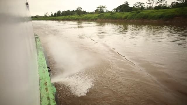Mid Shot water is gushing out from the side of the riverboat as it moves across the Amazon A transport riverboat travels in the Brazilian Amazon from...