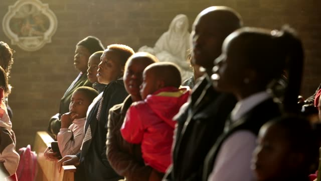 Mid to long zoom out shot The congregation pray during a Sunday service at Regina Mundi Church in Soweto on June 16 2013 in Johannesburg South Africa...