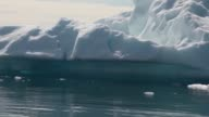 Mid Tracking Shot Calved icebergs from the nearby Twin Glaciers are seen floating on the water on July 30 2013 in Qaqortoq Greenland Boats are a...