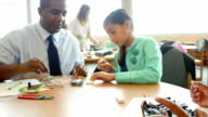Mid-adult African American male teacher helps pre-teen student with electrical components in STEM school library