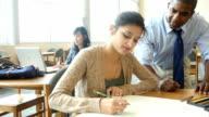 Mitte Erwachsenen afrikanische amerikanische Lehrer am Stiel school hilft weibliche hispanische student mit Projekt