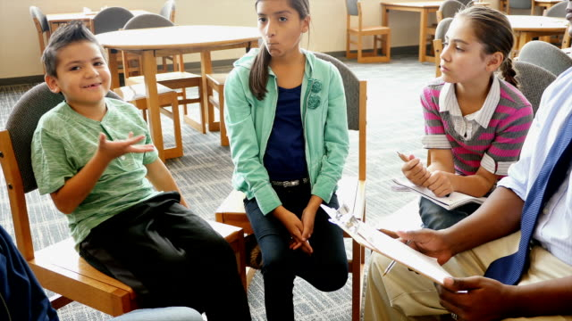 Mid-adult African American teacher facilitates discussion group in STEM school library