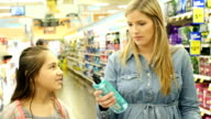 Mid-adult Caucasian mother and her Hispanic elementary age daughter shop in personal care aisle of supermarket