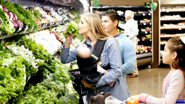 Mid-adult Caucasian mother and mid-adult Hispanic father shopping with three young daughters in local supermarket