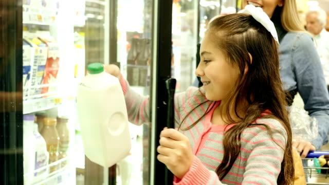 Mitte Erwachsenen europäischer Abstammung Mutter Einkaufen mit Hispanic Kind im Grundschulalter Tochter in Molkerei-Abschnitt in einem Lebensmittelgeschäft