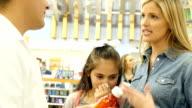 mid-adult europäischer Abstammung Mutter versucht Ratschläge von Mitte Erwachsenen antike Apotheker über Ihre Hispanic Kind im Grundschulalter Tochter das kalte Symptome