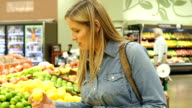 Mid-adult Caucasian pregnant woman picks out lemons in produce section of local grocery store