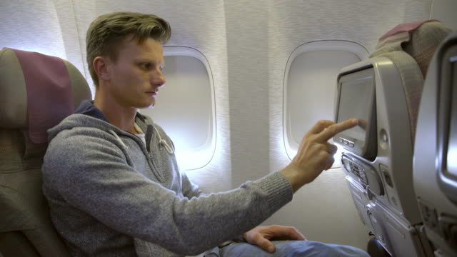 MS Mid-adult man using In-flight entertainment