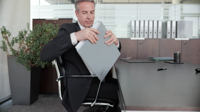 Middle aged businessman throwing a ring binder into the trash bin