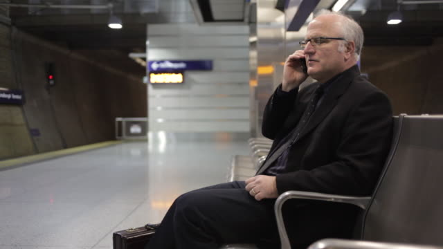MS Middle aged businessman using cellular phone inside commuter transit station / Minneapolis, Minnesota, United States