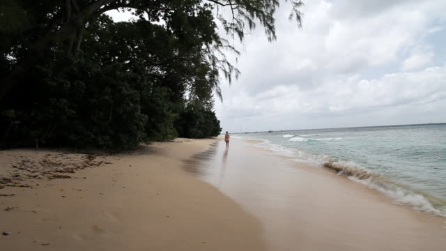 MS Middle aged lady walking away on ocean beach / Holetown, St. James, Barbados