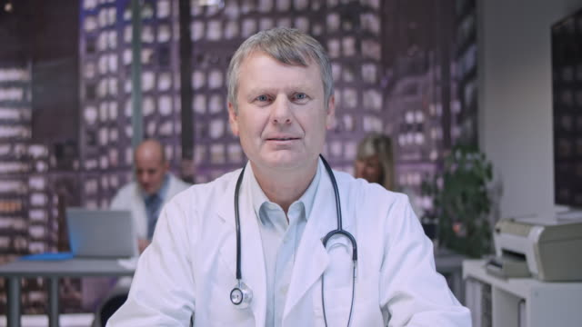 Middle aged male doctor on a video call from his office