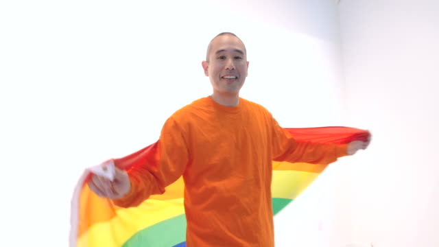 Mittleren Alter Mann spinning im circle mit gay-pride-Flagge