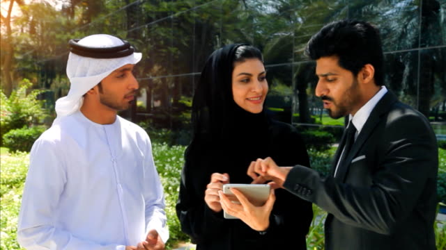 Middle Eastern Businessmen and Businesswoman working with Digital Tablet Outdoor