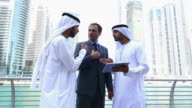 Middle eastern businessmen discuss with western man