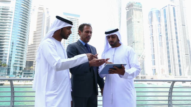 Middle eastern businessmen discussing with western man