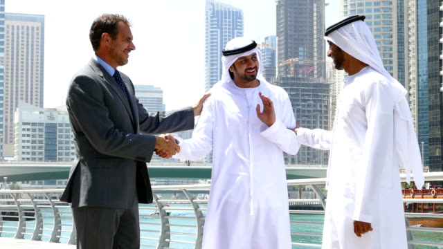 Middle eastern businessmen talking with western man