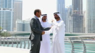 Middle eastern businessmen with western man outdoor