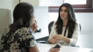 Middle Eastern female executive explains idea to African American female colleague