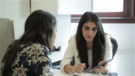 Middle Eastern female executive shows idea on digital tablet to African American female colleague