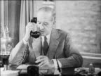B/W 1929 middleaged businessman smoking while talking on telephone in office / newsreel