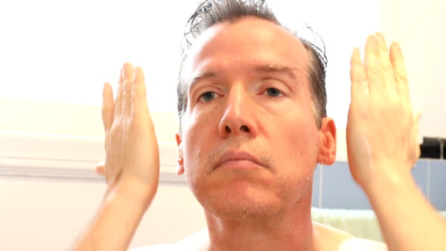 Middle-aged Caucasian male applying moisturizing anti aging product HD