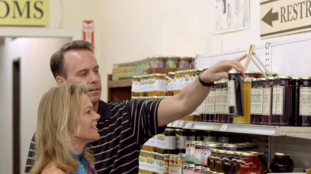 MS middle-aged couple in grocery store browsing shelves stocked with compote in glass jars / Cabazon, California, USA