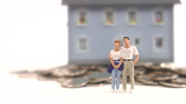 Middle-aged couple standing in front of a house.
