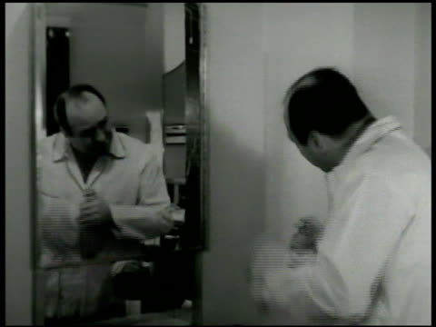 DRAMATIZATION Middleaged man w/ receding hairline standing in front of mirror looking at bottle of hair tonic shaking bottle rubbing some into hair...