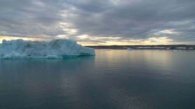 Midnight sun sailing with big icebergs in foreground Greenland