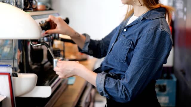 Buik van vrouwelijke Barista maken van koffie op Cafe