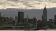 A midtown early morning skyline featuring Chrysler and The Empire States Building.  A tug boat crosses the frame.