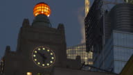 A midtown high rise clock tower close to Time Square.  The globe on top of the building blinks