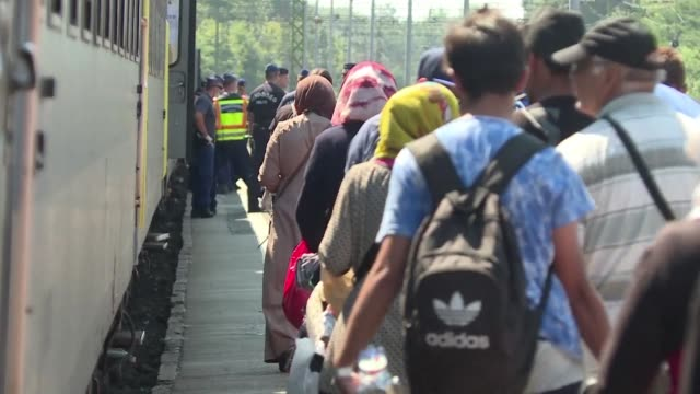 Migrants crossing from Serbia into Hungary are being directed from temporary holding camps onto trains heading north