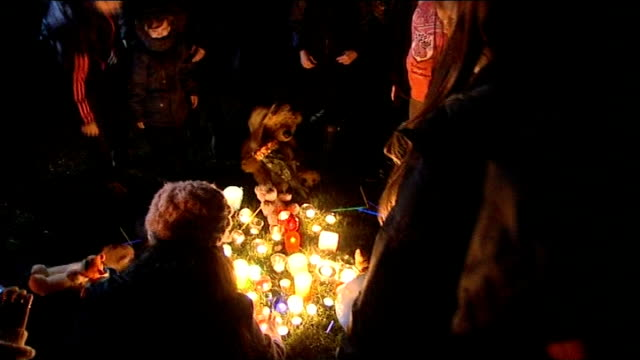 Mother due in court charged with his death NIGHT People placing candles at makeshift memorial for Mikaeel Soft toys and floral tributes on ground...