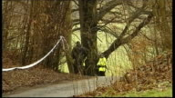 Mother due in court charged with his death Police officers and cordon tape in woods Police officers and police dog along by house