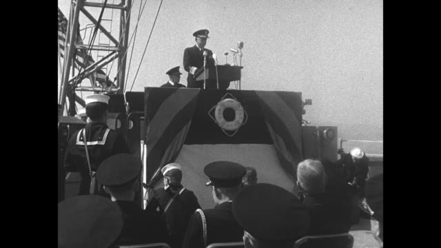 MS military audience watches ceremony on board USS Wisconsin / LS Vice Admiral Robert Briscoe speaks at microphone bank on dais as audience looks on...