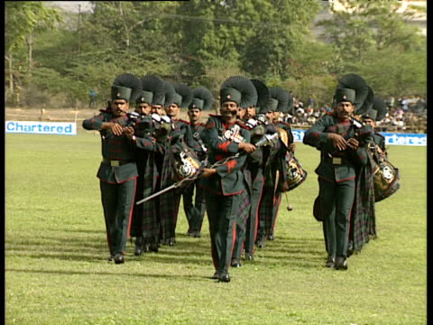 Military band in traditional uniforms marches towards camera then split into formation Royal Tour of India; Feb 92
