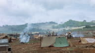 S military camp of pup tents a parked Jeep and smoking campfires during WWII Pacific campaign