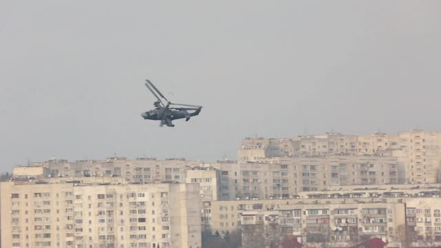 military helicopter patrols over the city