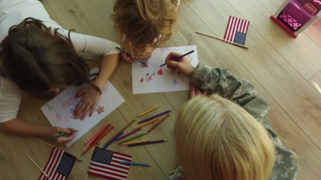 4K: militaire moeder kleuren met haar kinderen.