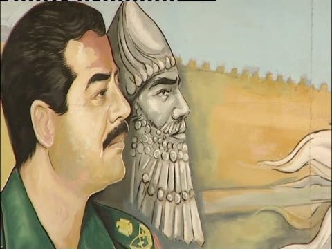 A military mural displaying Saddam Hussein covers a billboard in Iraq.