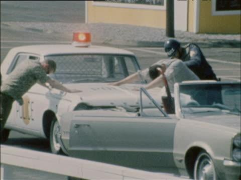 Military Police frisk men against car Riotsville Georgia 1968